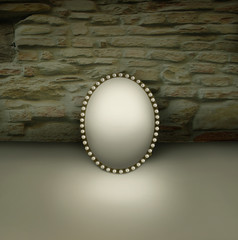 Small mirror with vintage frame decorated in pearls resting on a floor and with  brickwall background