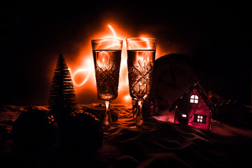Two glasses of champagne with Christmas decoration. Traditional winter holiday alcohol drink in snow with creative New Year artwork. Copy space.