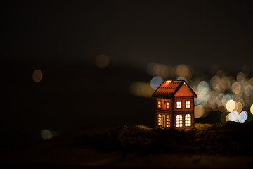 Little decorative house, beautiful festive still life, cute small house at night, Night city real bokeh background, happy winter holidays