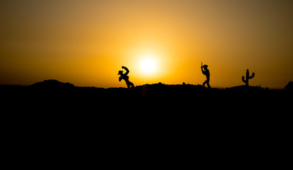 Cowboy concept. Silhouette of Cowboys at sunset time. Cowboys silhouettes on a hill with horses.