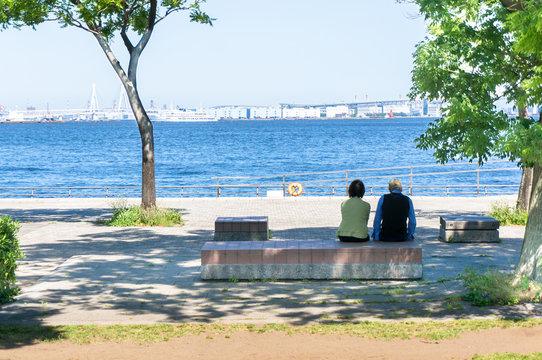 海辺の公園でベンチに座る老夫婦の後ろ姿
