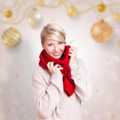 lächelnde junge Frau im Winterpullie und Schal vor weihnachtlichem Hintergrund