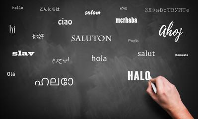 Hand schreibt das Wort Hallo in vielen Sprachen auf eine Kreidetafel