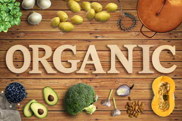 """Word """"Organic"""" in wooden letters with many cooking ingredients"""