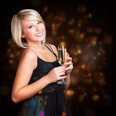 junge lächelnde Frau mit Sekt vor Silvesterhintergrund