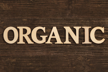 """Word """"Organic"""" in wooden letters on dark wooden background"""