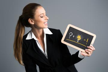 junge Geschäftsfrau mit Schiefertafel und Gleichung zur Ideenfindung