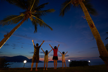 The family raised their hands and cheered to enjoy the seaside at dusk