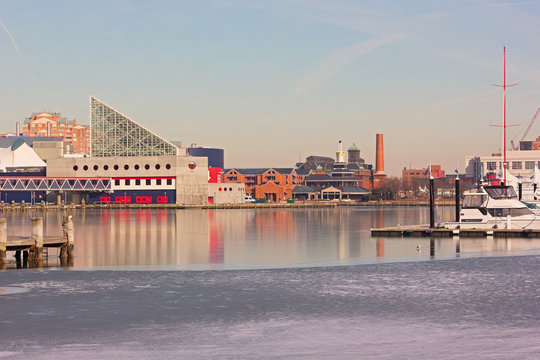 Baltimore Inner Harbor panorama before a winter sunset. City buildings along harbor piers with reflection in ice, Maryland, USA.