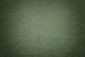 Texture of old dark green paper background, closeup. Structure of dense deep bluish cardboard.