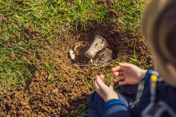 The boy plays recycling. He buries plastic disposable dishes and biodegradable dishes.  biodegradable dishes began to decompose and plastic did not