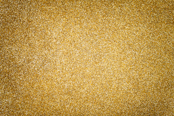 Golden sparkling background from small sequins, closeup. Brilliant backdrop.