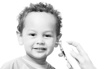 little boy having his temperature taken with digital ear thermometer