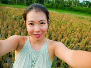 young happy and attractive Asian Korean woman taking selfie self portrait with mobile phone at tropical island posing cheerful and relaxed exploring rice field enjoying holidays