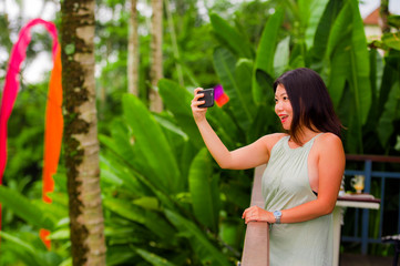 young happy and attractive backpacker Asian Chinese woman taking selfie self portrait with mobile phone at tropical island posing cheerful and relaxed exploring jungle