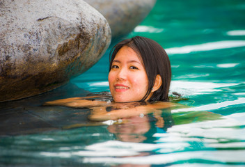 young attractive and beautiful Asian Korean woman relaxing happy at tropical beach luxury resort swimming at jungle infinity pool enjoying holidays in paradise island