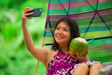 young beautiful and happy Asian Chinese tourist woman drinking coconut water taking selfie picture with mobile phone at luxury tropical island resort swimming pool