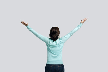 A brunette girl in a mint-colored jumper stands against the background gray. The young woman raised her hands up