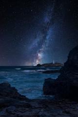 Vibrant Milky Way composite image over landscape of Godrevy lighthouse on Cornwall coastline in England