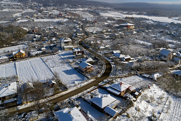 drone aerial view with houses and road in winter season