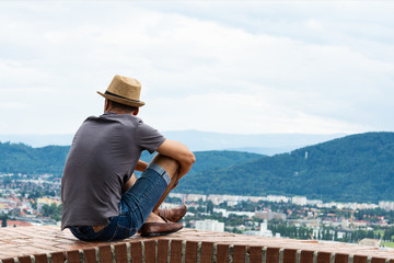 A young guy in comfortable moccasins sits on the edge of a tall building and looks at the mountains and the city of Graz Wall mural