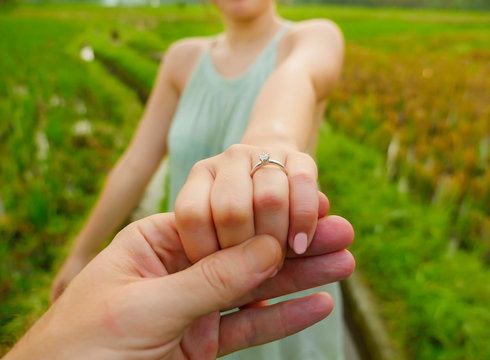 close up couple hands man holding happy fiance hand with diamond engagement ring on her finger after wedding proposal at tropical beautiful and romantic spot