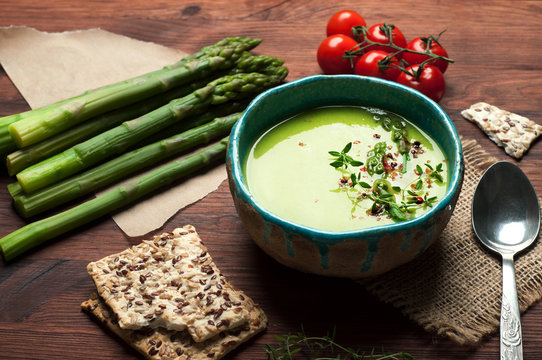 Cream soup with asparagus and cream, near boiled asparagus, tomatoes and diet breads. Useful and tasty low-calorie diet dinner