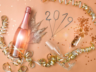 new year background with bottle of champagne on bronze, gold, brown background with different New Year's Eve items