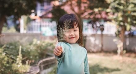portrait of happy asian little girl hand holding grass flower.