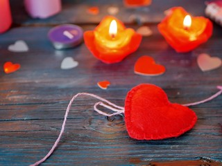 Valentine's Day decor on a wooden text table, a big red heart of felt and small paper hearts, red burning candles, a top view