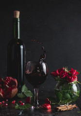 Red wine in a glass. Romantic evening with a glass of wine to Valentine's day.Holiday composition on a black table  and  background. Splash of drink