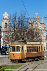 Old tram with famous church Igreja do Carmo dos Carmelitas in Ribeirain Porto, Portugal.