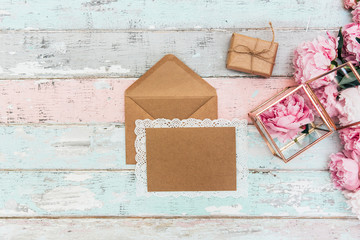 Mockup  greeting card and envelope with pink peonies on a vintage background