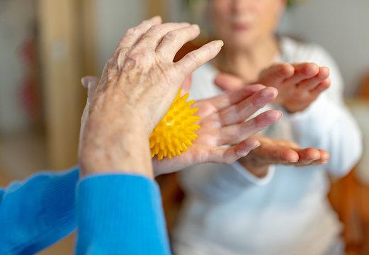 Rentnerin macht Lockerungsübungen mit einem Igelball