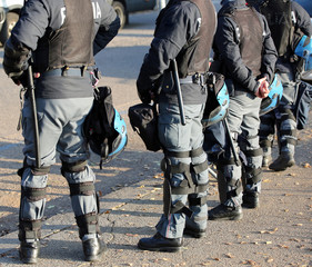 police in riot gear with flak jackets and protective helmets