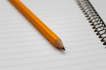Yellow pencil on the background of a lined sheet of notebook on a spiral close-up and copy space