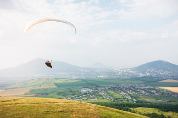 Professional paraglider in a cocoon suit flies high above the ground against the sky and fields with mountains