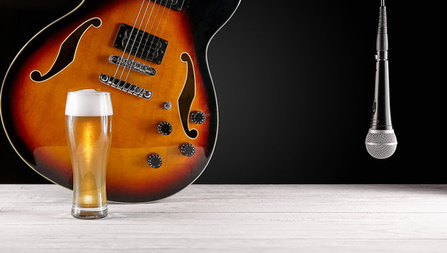 Glass of beer and microphone near electric jazz guitar on white wooden desk. Dark background