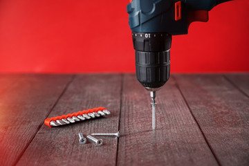 Twisting screw with blue electric screwdriver into  black wood. close-up. Red background