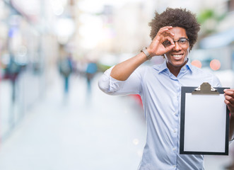 Afro american man holding clipboard over isolated background with happy face smiling doing ok sign with hand on eye looking through fingers