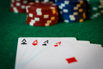 Four aces on the poker table with chips