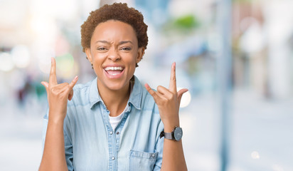 Young beautiful african american woman over isolated background shouting with crazy expression doing rock symbol with hands up. Music star. Heavy concept.