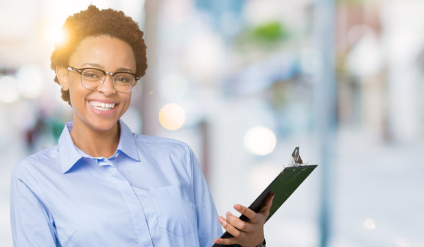 Young african american businesss woman holding clipboard over isolated background with a happy face standing and smiling with a confident smile showing teeth