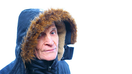 senior man in a blue warm winter jacket, hood with natural fur on his head, isolated on a white background, looking with one eye, the other eye hidden under the hood