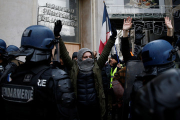"""People face off with French Gendarmes as they demonstrate during a national day of protest by the """"yellow vests"""" movement in Paris"""
