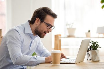 Excited male worker look at laptop screen reading breaking news, surprised man using computer get unexpected email offer or promotion letter, lucky employee feel euphoric win lottery online