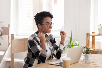 Fototapeta Excited African American woman in glasses read good news online at laptop, happy black female get promotional letter or email celebrating goal achievement, smiling girl look at computer lucky with win obraz