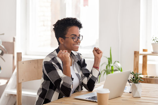 Excited African American woman in glasses read good news online at laptop, happy black female get promotional letter or email celebrating goal achievement, smiling girl look at computer lucky with win
