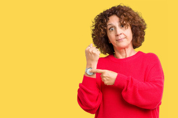 Beautiful middle ager senior woman red winter sweater over isolated background In hurry pointing to watch time, impatience, upset and angry for deadline delay