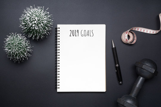 2019 new years resolutions sport flat lay composition. Black dumbbells, measuring tape, blank notebook and mini Christmas tree on black background. New year new healthy and dieting goals concept.